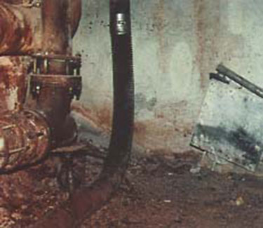 Old ceramic, refractory-type elbow is shown above. Material blown out from frequent plug-ups can still be seen on the floor and pipes.